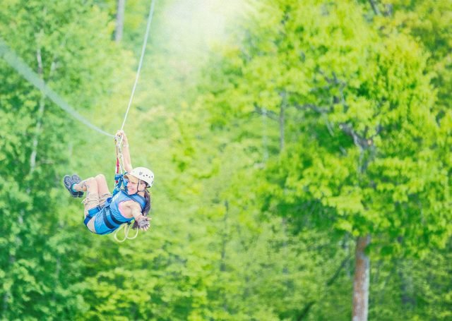 person swings on zip line over trees