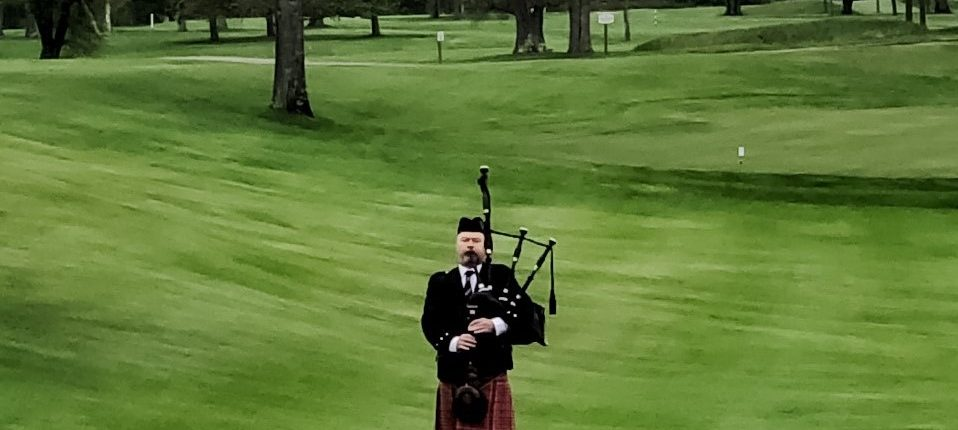 bagpiper plays from golf course