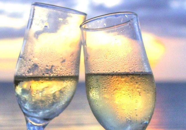 two champagne glasses clink by sunset