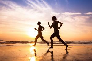 Two people run on the beach