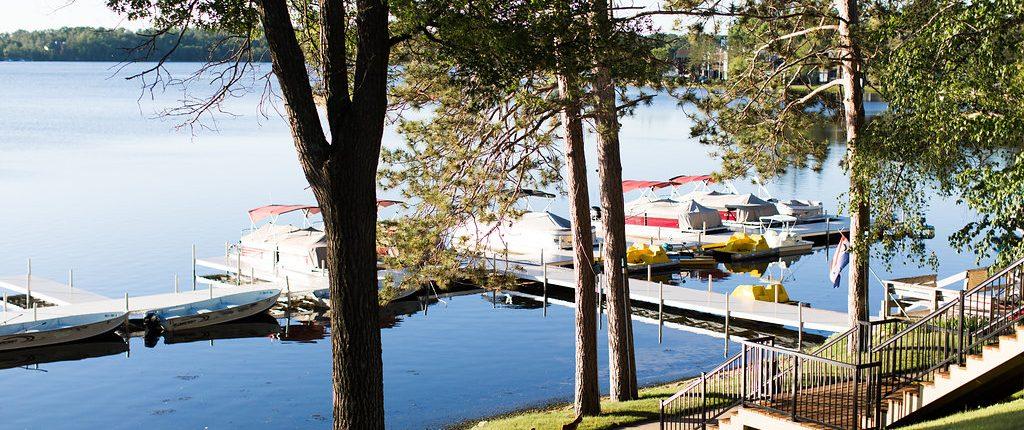 pontoon boats wait at dock on lake