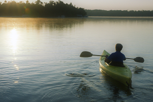 person kayaks on lake