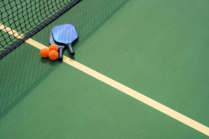 pickleball table with rackets and balls