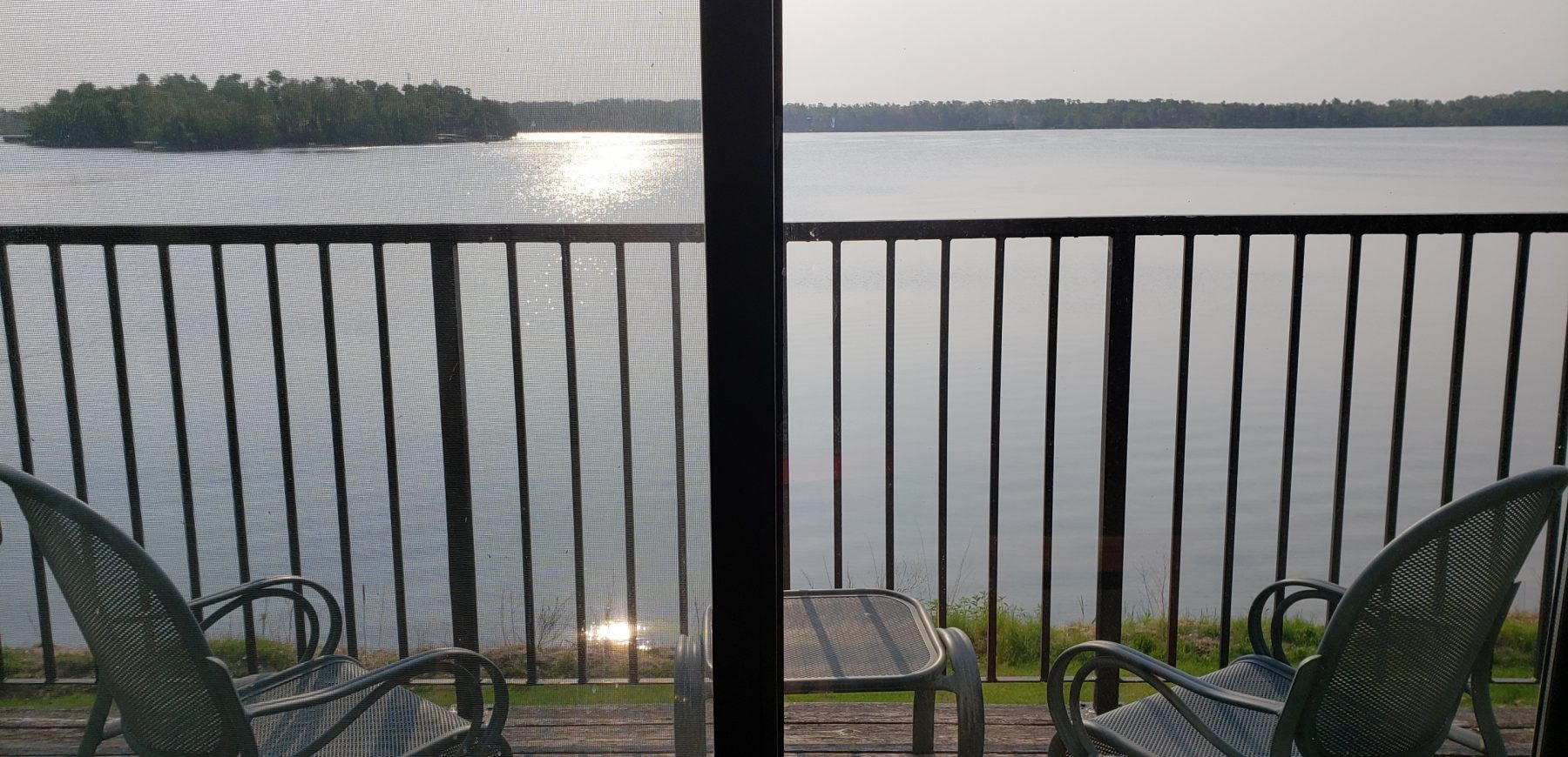 two chairs on a deck overlooking a lake