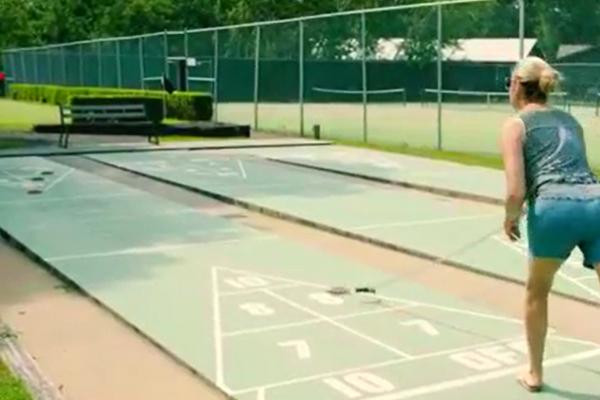 person plays shuffleboard