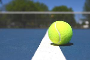 tennis ball on blue tennis court