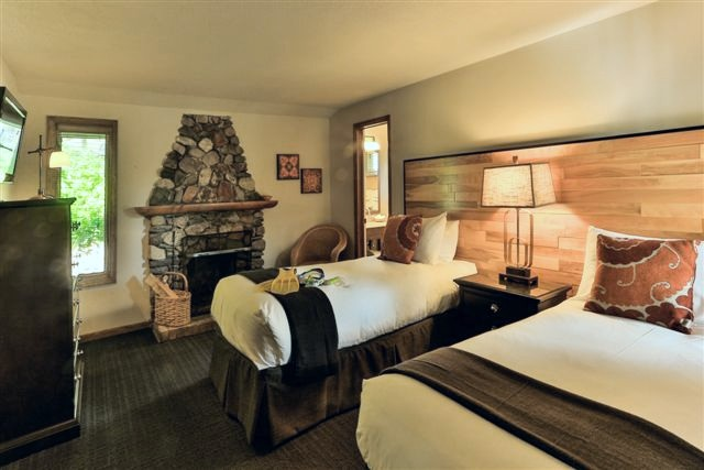 two bed hotel room with rock fireplace