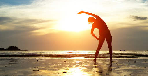 person stretches on the beach