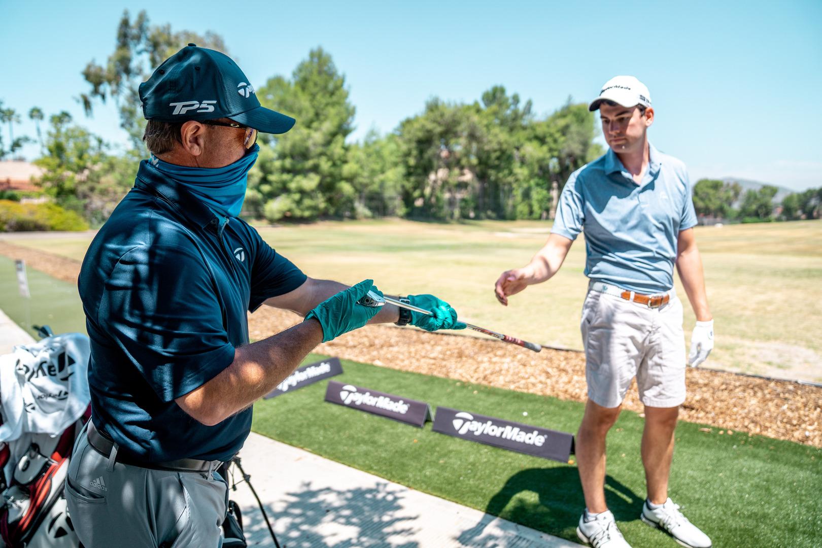 caddy hands a golfer a golf club
