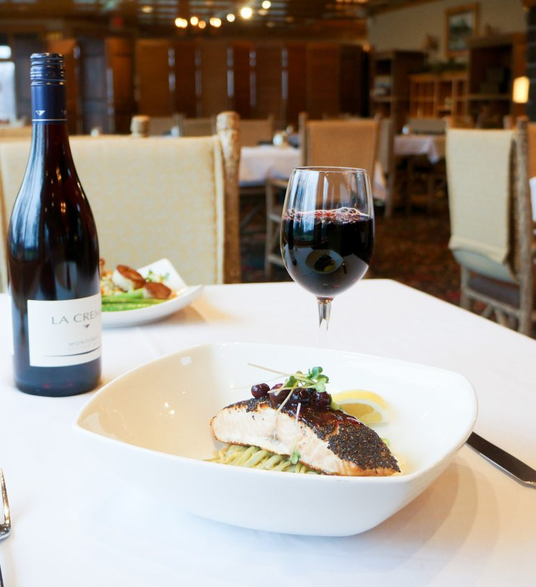 salmon dish with red wine on a table