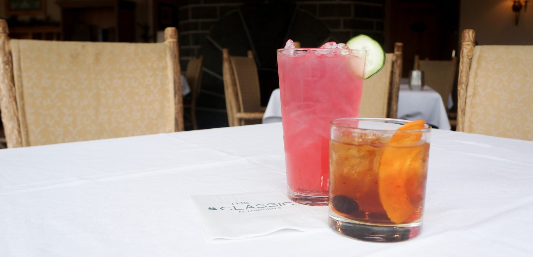 two cocktails on a while linen clothed table