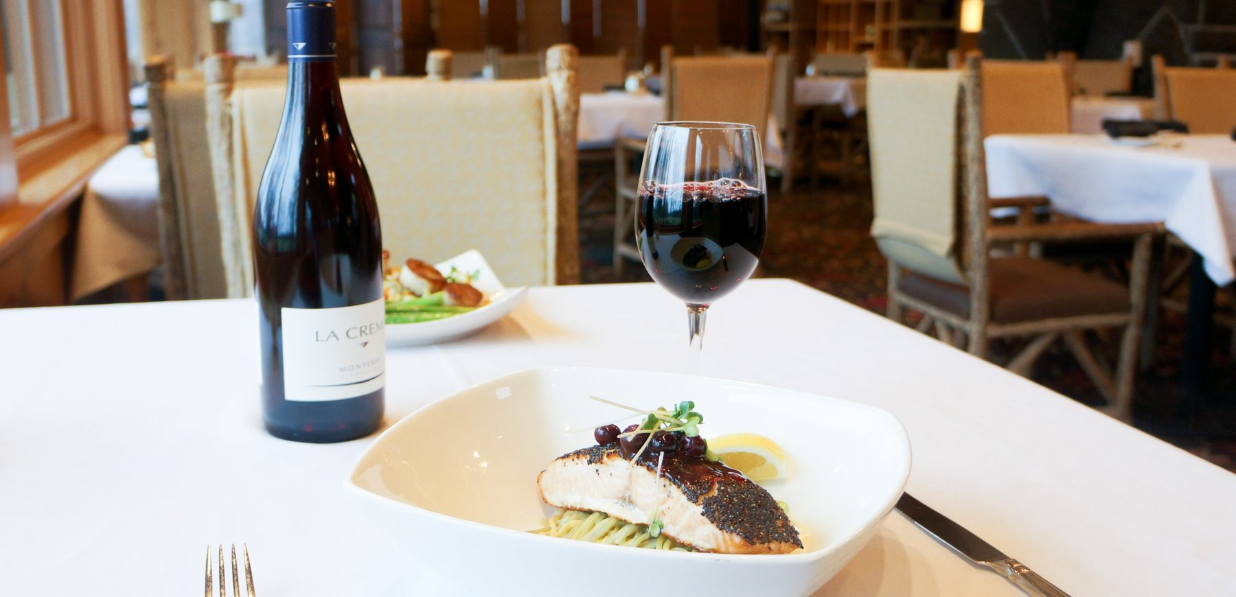 poppyseed salmon dish with glass of red wine