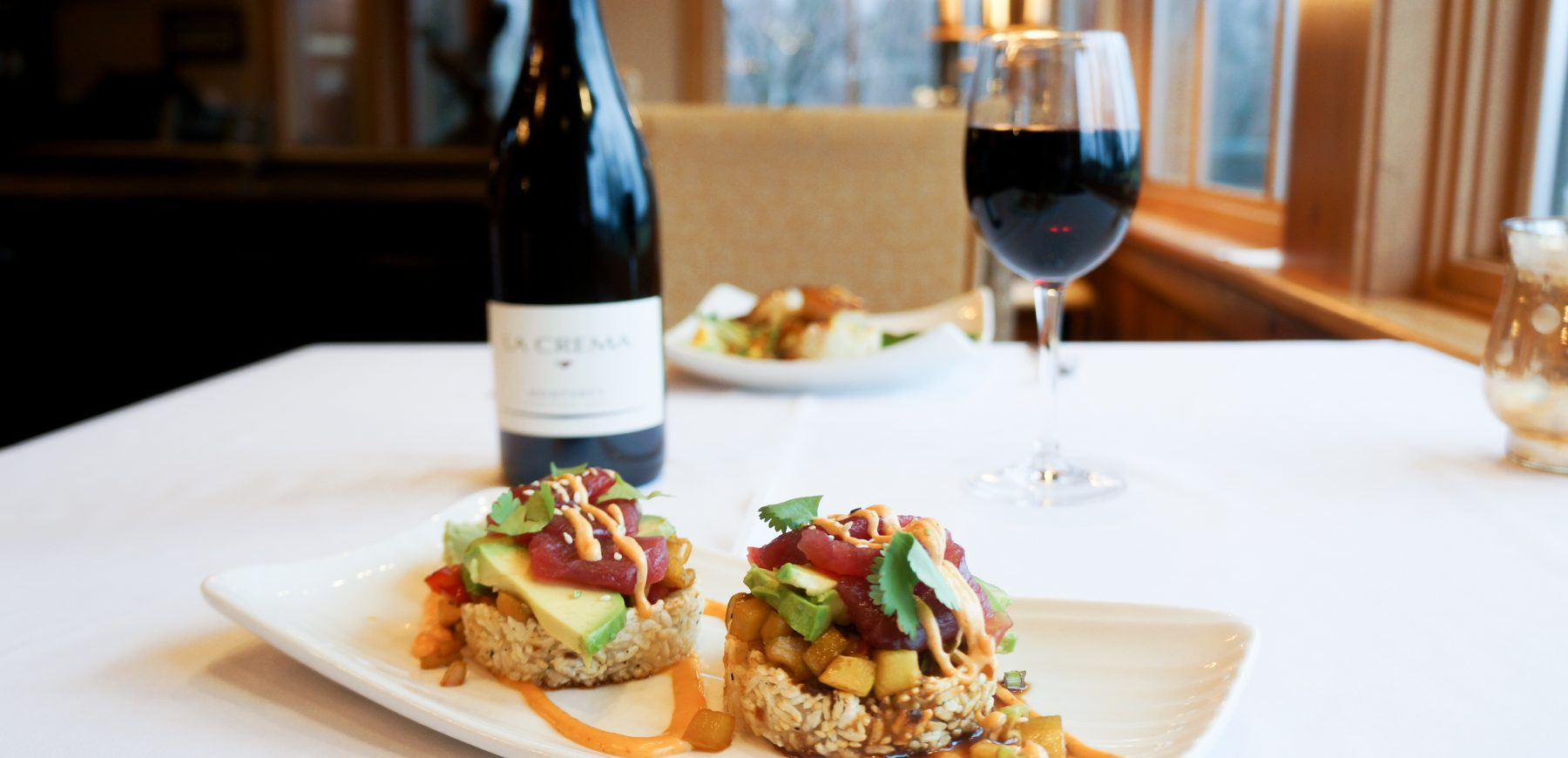 grilled sushi stacks with glass and bottle of red wine