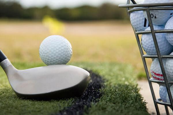 golf ball rests on club