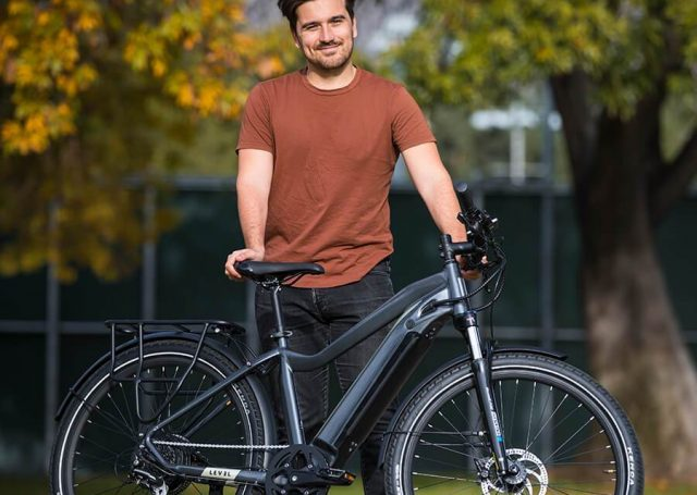 smiling man stands with bicycle