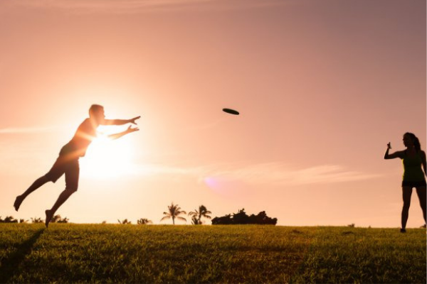 two people play frisbee at sunset