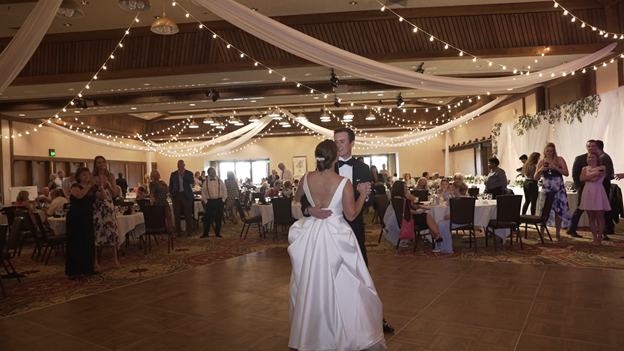 bride and groom dance their first dance while guests surround them