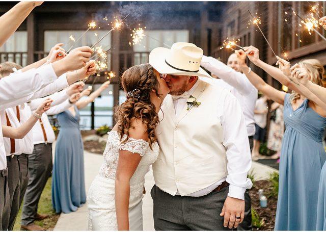 bride and groom kiss under sparklers held aloft