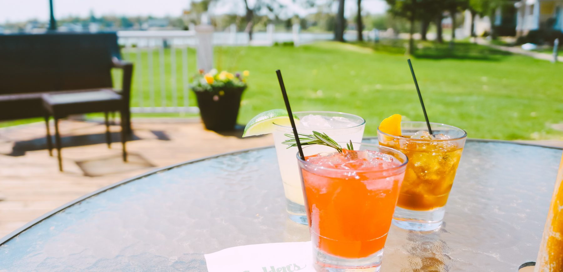 three cocktails on an outside patio table