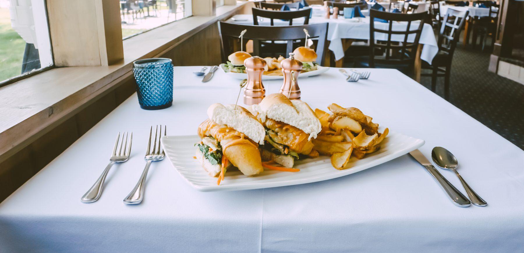 crispy cod roll sandwich with potato wedges