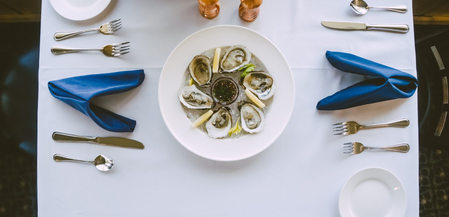 plate of oysters on a table at a restaurant with two place settings