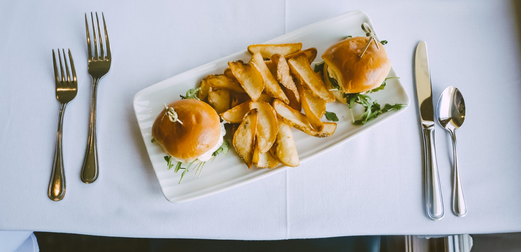 plate of two shrimp sliders and potato wedges