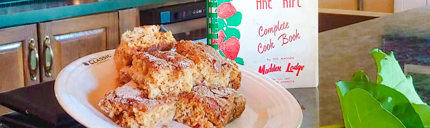 squares of rhubarb cake with fresh pieces of rhubarb and a cookbook