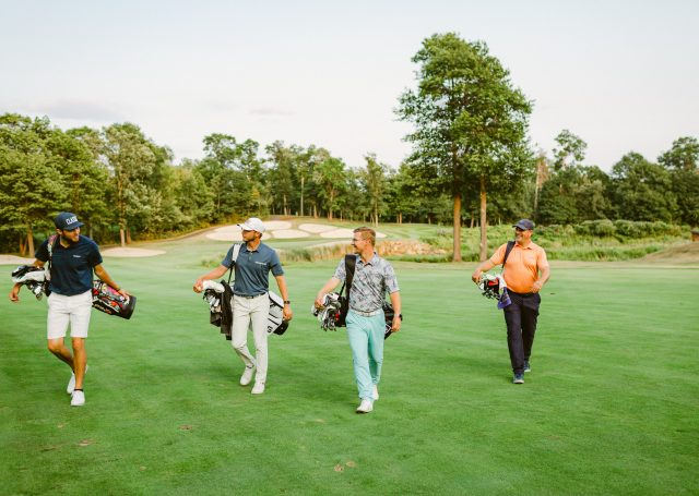 four golfers carrying their clubs walk off golf course